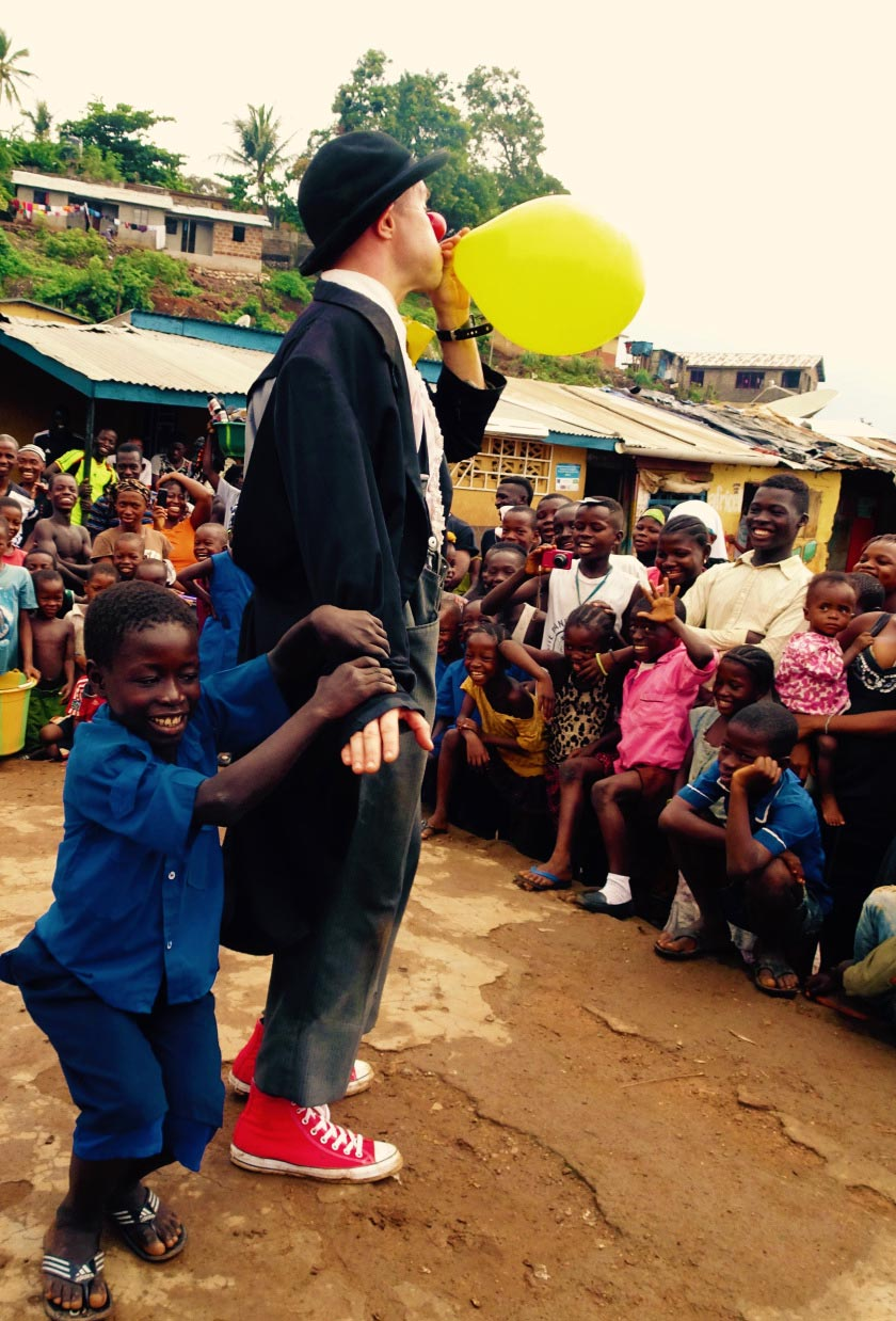 Tim Cunningham performs the ever-popular balloon trick with help from a young participant in Sierra Leone.