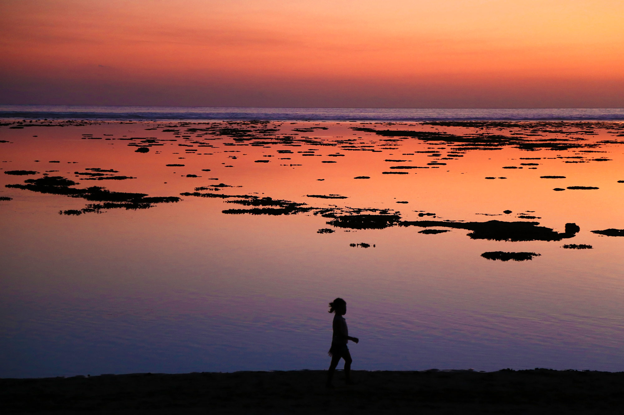 The sun sets on Reunion Island, silhouetting a young girl playing on the beach. (Photo by Heather Mason)