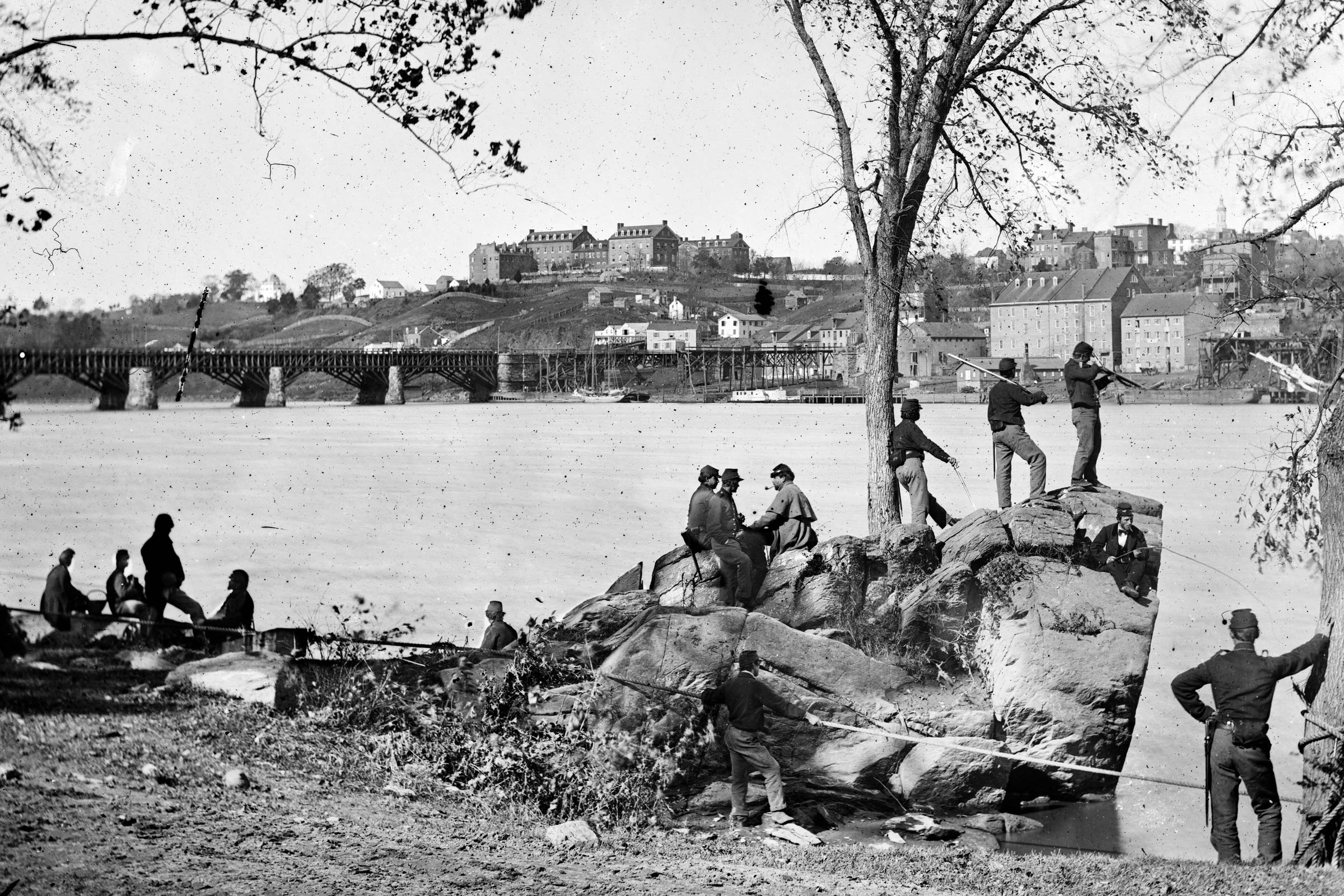 Union soldiers on Mason's Island (later Theodore Roosevelt Island) in Washington in 1861. Behind them is the Potomac Aqueduct Bridge; Georgetown University is on top of the hill. The island served as a storage and distribution site and also as a Union tra