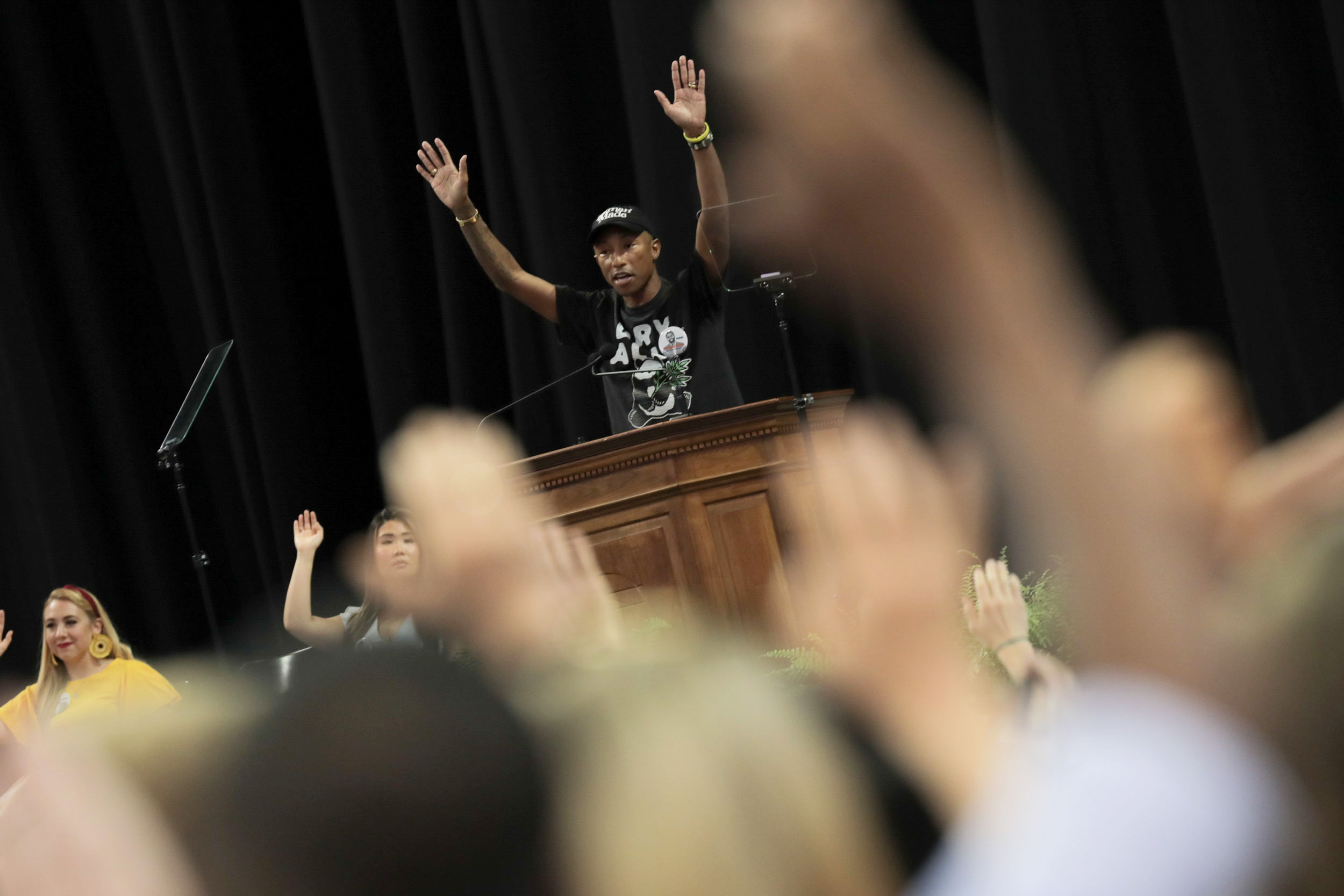 Pharrell Williams raised both hands in solidarity with a huge audience, who attended his Valedictory address Friday afternoon at John Paul Jones Arena. (Photo by Sanjay Suchak, University Communications)