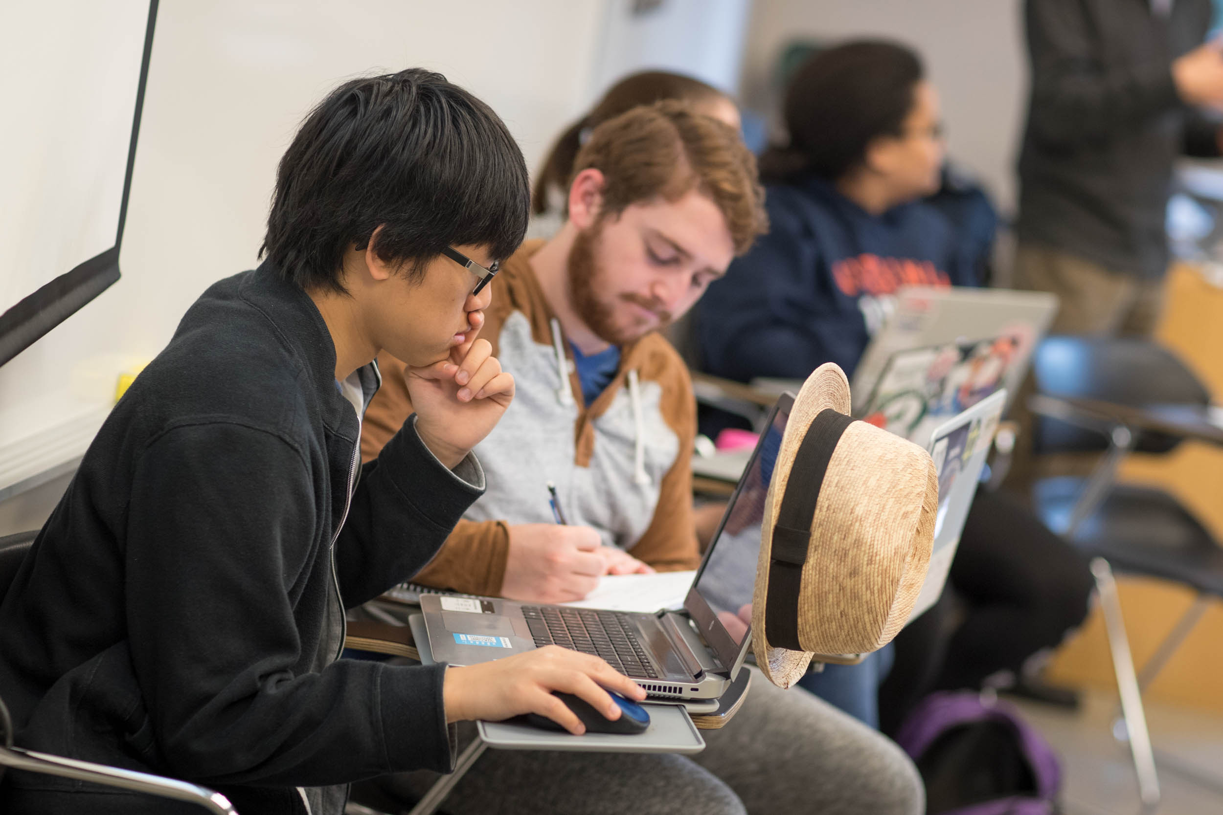 Thuy Vuong, seated in his class at UVA, is taking the course with his brother, Huan, who is a member of The Tribe. (Photo by Sanjay Suchak, University Communications)