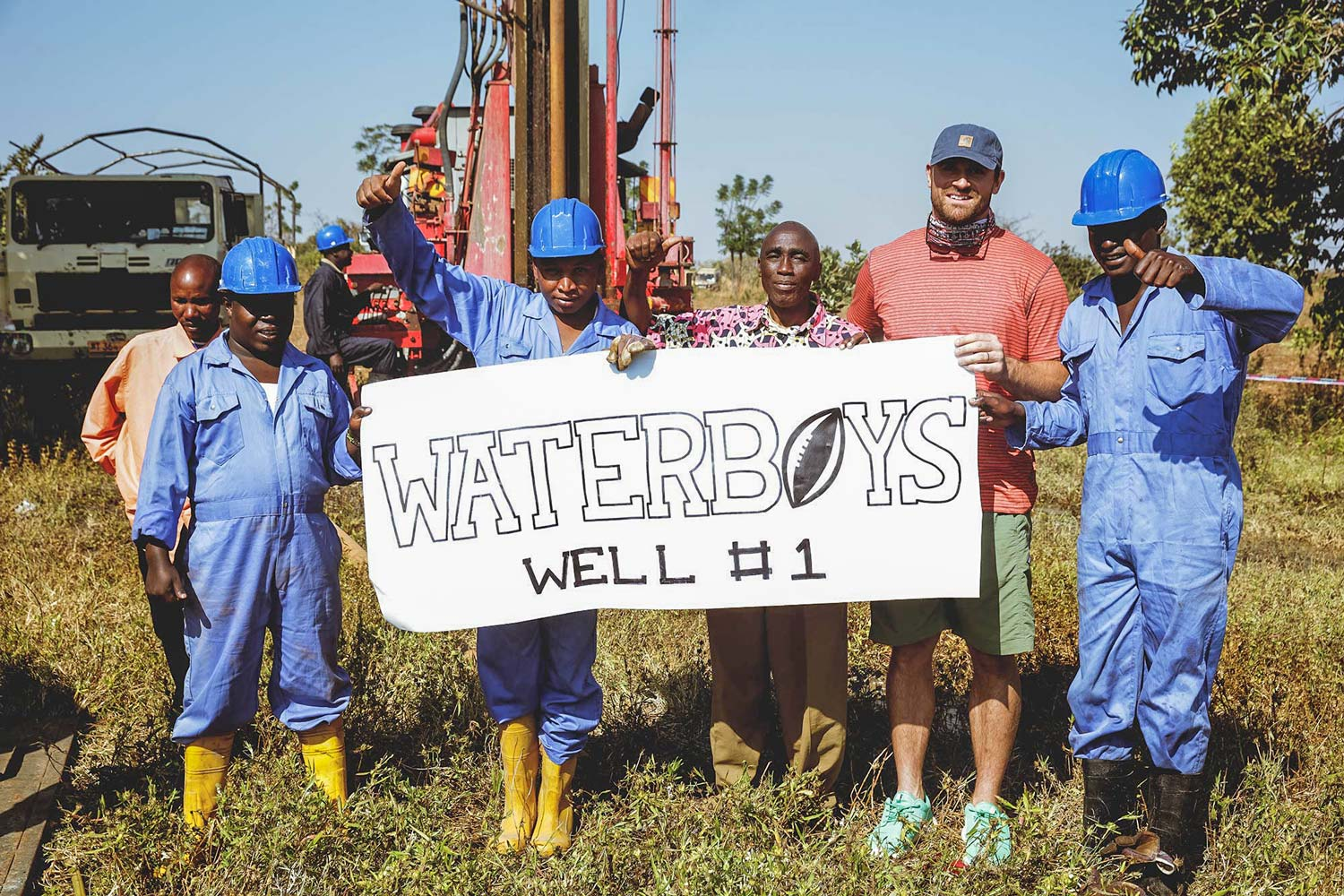 Chris Long, second from right, celebrates with workers after the completion of the first well in Tanzania.