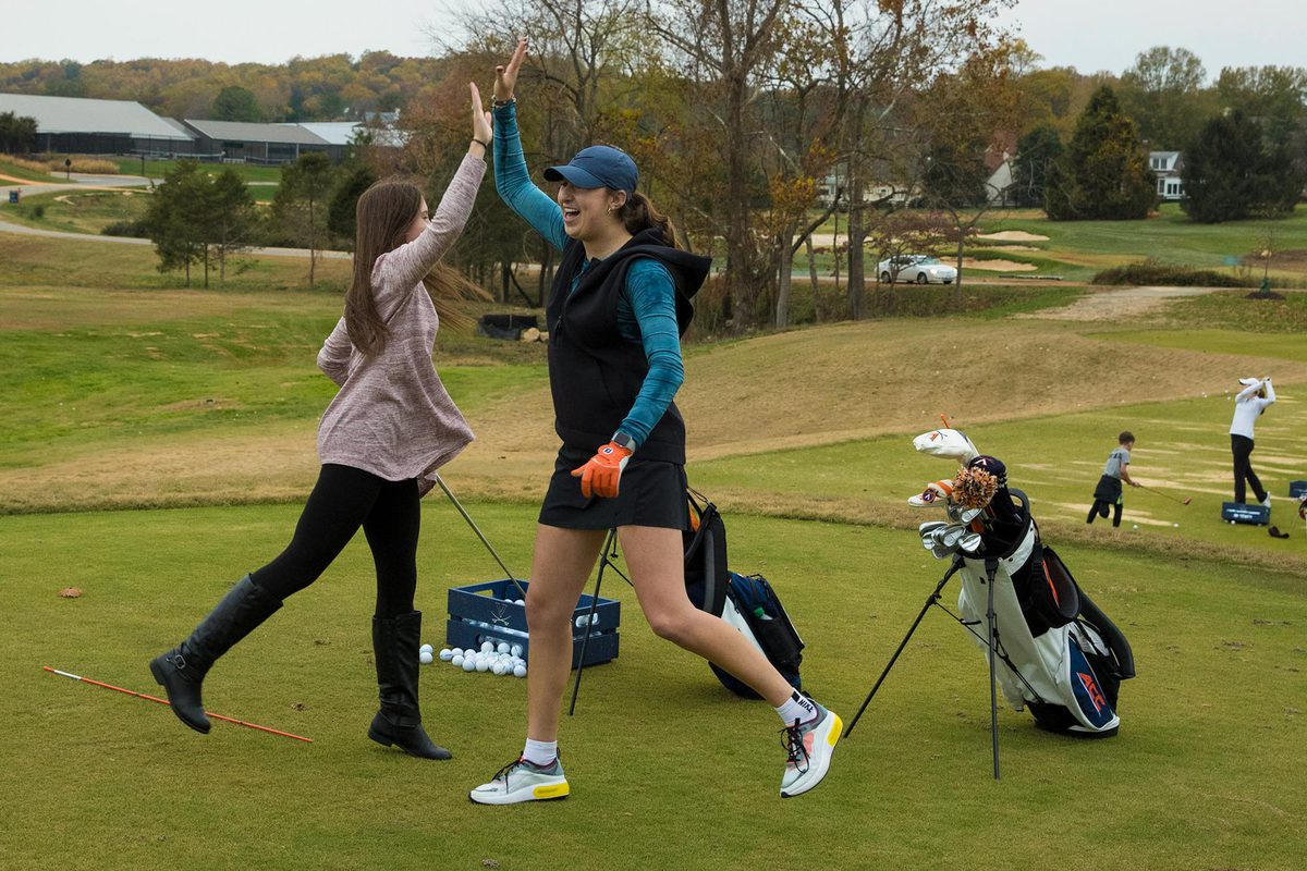 UVA golfer Sky Sload celebrates a good shot with teaching assistant Molly Harry.
