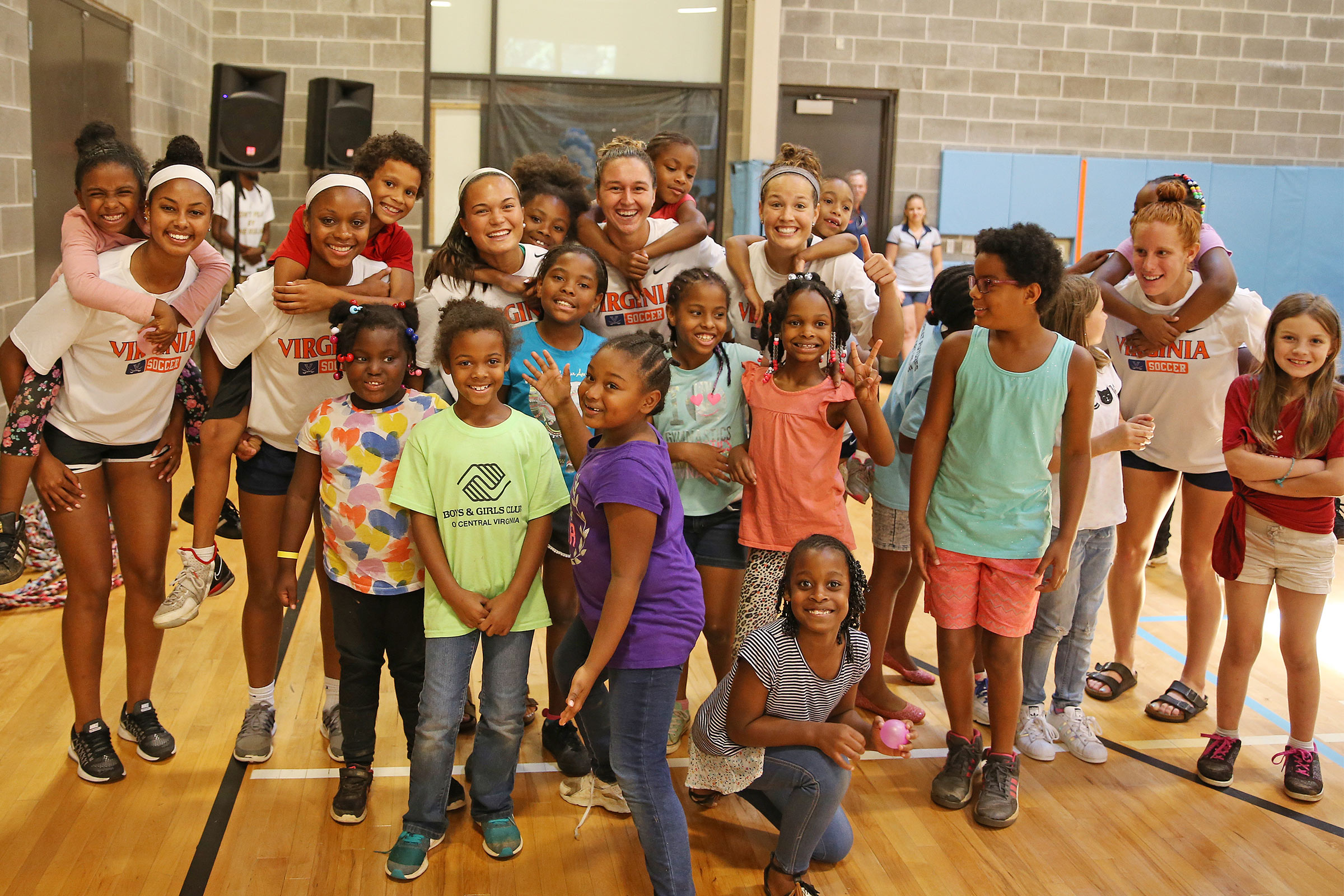 Members of the women's soccer team with children at the Boys and Girls Club Cherry Avenue.