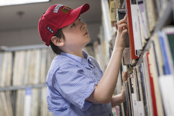 Kieran Garrod searches for a record in WTJU's extensive library of vinyl records during one of the station's summer camp sessions for middle- and high-school students.