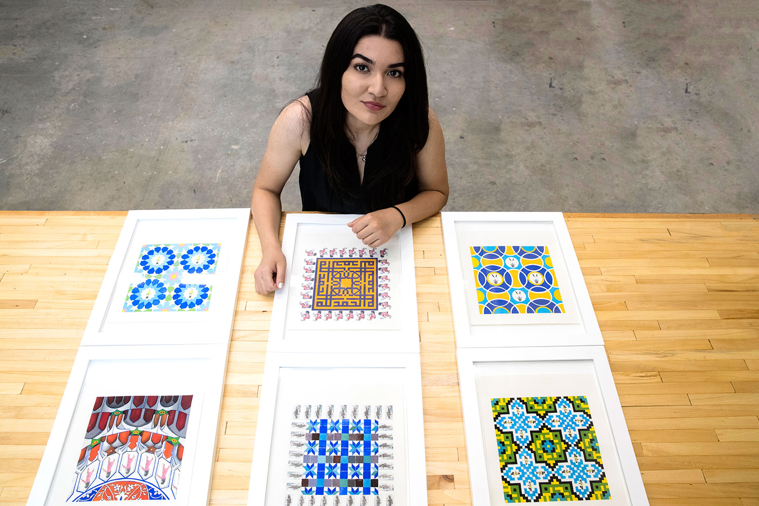 "Feraidon with the paintings in her ""Hide and Seek"" series. She used photos of Afghan women to create some of the patterns seen here, including the borders of the two paintings in the middle row and the central figures of paintings in the first and third rows. (Photo by Dan Addison, University Communications)"